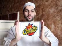 Churchs chicken logo. Logo of food franchise and restaurant churchs chicken on samsung tablet holded by arab muslim man Royalty Free Stock Photo