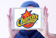 Churchs chicken logo. Logo of food franchise and restaurant churchs chicken on samsung tablet holded by arab muslim woman Royalty Free Stock Images