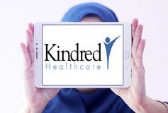 Kindred Healthcare logo. Logo of Kindred Healthcare on samsung tablet holded by arab muslim woman. Kindred Healthcare Incorporated is a healthcare services Royalty Free Stock Images
