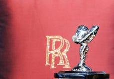 Logo Luxusautos Royce und rote Satinrückenlehne pillow mit Klotz Lizenzfreies Stockfoto