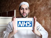 National Health Service , NHS , logo. Logo of National Health Service , NHS , on samsung tablet holded by arab muslim man. The National Health Service NHS is the Stock Photos