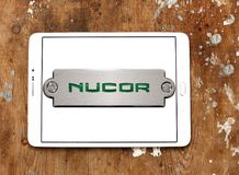 Nucor steel Corporation logo. Logo of Nucor steel on samsung tablet on wooden background. Nucor Corporation is a producer of steel and related products. It is Stock Photo