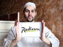 Radisson Hotels logo. Logo of Radisson Hotels on samsung tablet holded by arab muslim man. Radisson Hotels is an international hotel company and a subsidiary of stock image