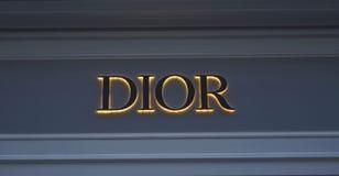 Logo rougeoyant sur la marque DIOR de mur photographie stock