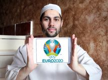 UEFA Euro 2020 logo. Logo of UEFA Euro 2020 on samsung tablet holded by arab muslim man. The 2020 UEFA European Football Championship is scheduled to be the 16th Royalty Free Stock Photo