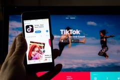 Logo vidéo-partageant mobile de société d'appli de TikTok sur l'écran de téléphone avec la page d'accueil d'Internet à l'arrière- photos libres de droits