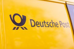 Logo von Deutsche Post und von DHL auf gelbem postcar lizenzfreies stockfoto