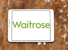 Waitrose Supermarkets chain logo. Logo of Waitrose Supermarkets chain on samsung tablet on wooden background . Waitrose is a chain of British supermarkets, which Stock Image
