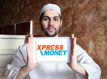 Xpress Money company logo. Logo of Xpress Money company on samsung tablet holded by arab muslim man. Xpress Money is a global money transfer company royalty free stock photo