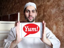 Yum! Brands logo. Logo of Yum! Brands on samsung tablet  holded by arab muslim man. is an American fast food company. A Fortune 500 corporation, Yum! operates Royalty Free Stock Photos