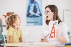 Logoped som arbetar med ett barn på ett korrekt uttal arkivfoto