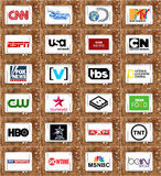 Logos of top famous tv channels and networks. Collection of logos and vectors of most popular television networks in the world on white tablet on rusty wooden Stock Photos