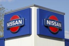 Logotecken av den Nissan bilåterförsäljaren Royaltyfri Bild