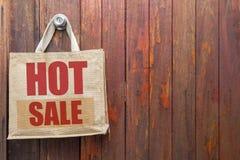 Logotipo caliente de la venta en el panier del yute que cuelga sobre viejo fondo de madera de la puerta Foto de archivo libre de regalías