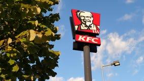 Logotipo da cadeia alimentar de fast food de KFC da empresa de Yum Brands com uma árvore e rapidamente de nuvens moventes em um c filme