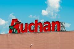 Logotipo de Auchan en la alameda de Promenada, cielo azul con las nubes blancas fotografía de archivo libre de regalías