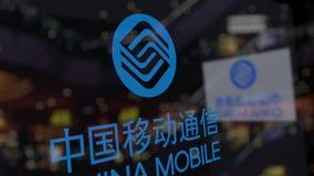 Logotipo de China Mobile sobre el vidrio contra centro de negocios borroso Representación editorial 3D Imagen de archivo libre de regalías