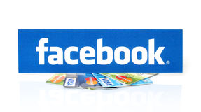 Logotipo de Facebook impreso en el papel y puesto en visa de las tarjetas y Mastercard en el fondo blanco Imagenes de archivo