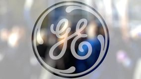 Logotipo de General Electric sobre un vidrio contra la muchedumbre borrosa en el steet Representación editorial 3D almacen de video