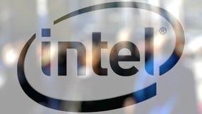 Logotipo de Intel Corporation sobre un vidrio contra la muchedumbre borrosa en el steet Representación editorial 3D stock de ilustración