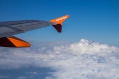 Logotipo de la compañía de EasyJet en aletilla de los aviones en el cielo azul y las nubes Fotografía de archivo libre de regalías