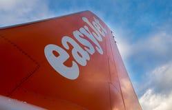 Logotipo de la compañía de EasyJet en la cola de los aviones en fondo del cielo azul Imágenes de archivo libres de regalías