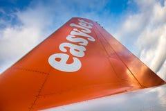 Logotipo de la compañía de EasyJet en la cola de los aviones en fondo del cielo azul Fotos de archivo libres de regalías