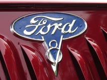 Logotipo de la compañía de Ford con las insignias de V8 en la capilla de un coche clásico en un salón del automóvil fotografía de archivo libre de regalías