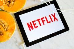 Logotipo de Netflix mostrado en la pantalla de la tableta con la fruta fresca imágenes de archivo libres de regalías