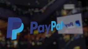 Logotipo de Paypal sobre el vidrio contra centro de negocios borroso Representación editorial 3D Imagen de archivo libre de regalías