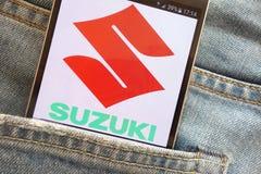 Logotipo de Suzuki Motor Corporation indicado no smartphone escondido no bolso das calças de brim fotografia de stock royalty free