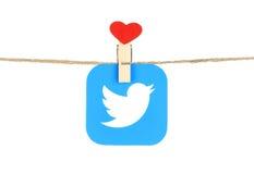Logotipo de Twitter, impreso en el papel, hangind en una cuerda con el corazón rojo foto de archivo