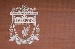 Logotipo del club del fútbol de Liverpool en el color blanco en fondo marrón de la pared de ladrillo usando imagen de archivo libre de regalías