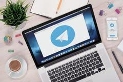 Logotipo del mensajero del telegrama en las pantallas del ordenador portátil y del smartphone Fotos de archivo