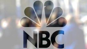 Logotipo do NBC de Nacional Transmissão Empresa em um vidro contra a multidão borrada no steet Rendição 3D editorial Fotos de Stock
