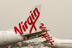 Logotipos das linhas aéreas de Austrália do Virgin em aviões. Imagens de Stock