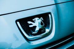 Logotype dell'automobile di Peugeot sulla nuova automobile in sala d'esposizione Immagini Stock Libere da Diritti
