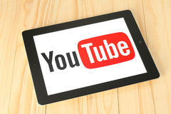 Logotype di YouTube sullo schermo del iPad su fondo di legno Immagini Stock
