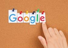 Logotype novo de Google impresso fixado no quadro de mensagens da cortiça com mão Fotografia de Stock Royalty Free