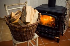 Logs. Basket with logs in front of stove Royalty Free Stock Photo