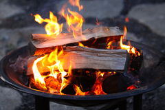 Logs Burning in a Fire Pit. Logs burning brightly in a fire pit is great on a cool night, at home or camping stock photos