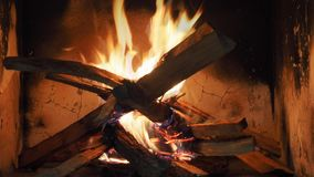 Logs burning in fireplace. With flames, smoke and glowing embers. Seamless loop stock footage