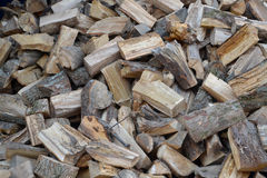 Logs of firewood lie on the earth, heaped. Background.  Royalty Free Stock Photography