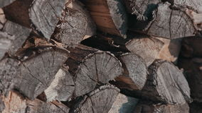 Logs of firewood neatly stacked in the woodpile in winter macro stock video footage