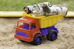 Logs in toy truck. Birch logs in colorful toy truck stock image