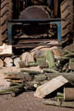 Logs and tractor driven saw. Wood for a log burner, sawn by a circular saw driven by a tractor. The wood is from broken fence posts and fallen trees royalty free stock photography