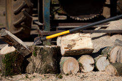 Logs and tractor driven saw with woodcutting axe. Wood for a log burner, sawn by a circular saw driven by a tractor. The wood is from broken fence posts and royalty free stock photography