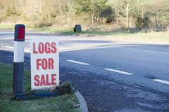 Logs wood for sale sign at farm shop for biomass burner. Uk royalty free stock photography