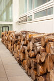 Logs woodpile near modern building house wall Royalty Free Stock Photography