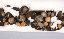 The logs woodpile in the snow in winter. Rural winter scene. HDR Stock Images